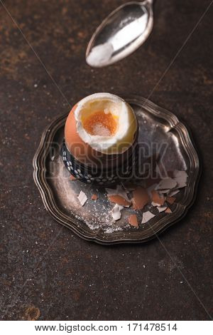 Soft-boiled egg on the metal background top view