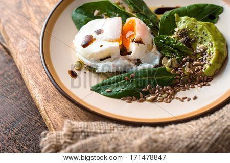 Poached egg with avocado cream sauce and spinach on the ceramic plate