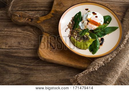 Poached egg with avocado cream and spinach on the old wooden table top view