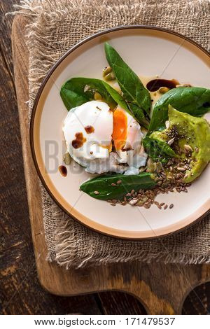 Poached egg with avocado cream sauce and spinach on the ceramic plate top view