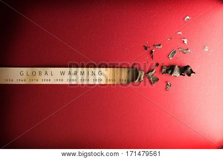 Global warming, Climate change, concept image. Rising temperature through the decades. Paper strip with timeline charred and burnt on the right end, placed on red background.