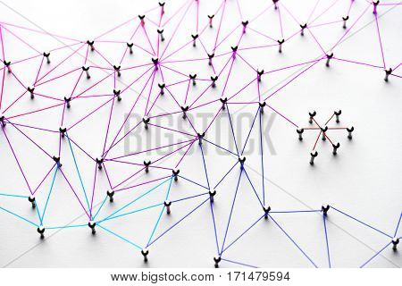Linking entities. Networking, social media, SNS, internet communication abstract. Small network connected to a larger network. Web of light to dark blue, red, purple, gold wires on white background.