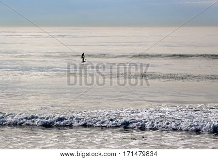 Silhouetted lone paddle-boarder rowing out into the shining sea, waves and horizon.