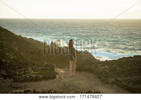 Pretty girl or beautiful woman sexy slim brunette stands on rocky beach at stormy blue sea on white sky background