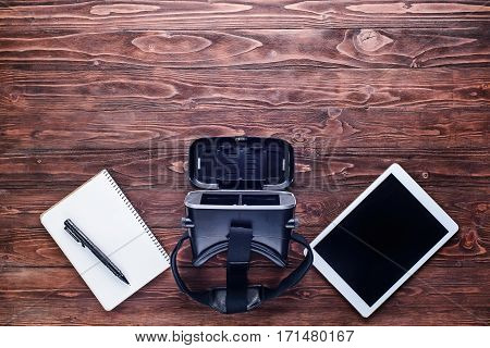 Tabletvirtual reality device and notebook with pen on wooden table.Top view