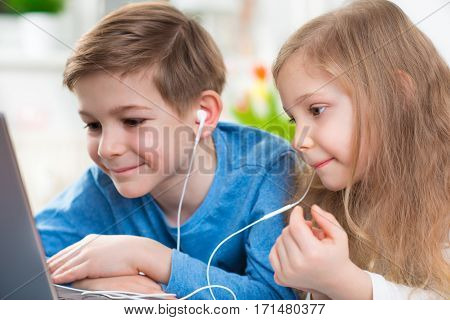 Two Happy Children Playing With Laptop And Listening Music With Headphones
