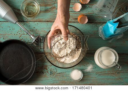 Adding flour in glass bowl for pancakes preparation top view