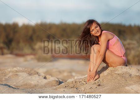 Beautiful young Woman posing in pink bikini again blue sky with sun