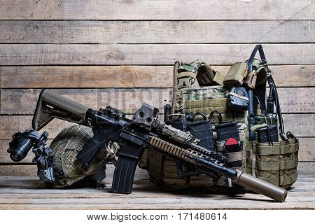 Flak jacket with ammo military equipment assault rifle and helmet on wooden background