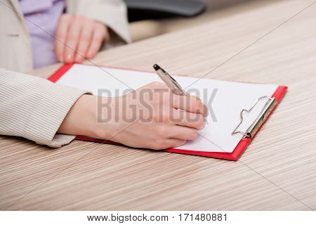 Hands taking notes in the pad