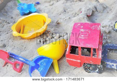 Children's bright plastic toys in sandpit sand