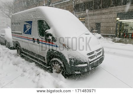 New York, February 9, 2017: A US Mail van that is parked in the street is getting buried by the falling snow.