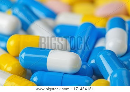 pile of medical pills and blue pills on a background;