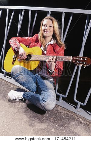 Happy Positive Caucasian Blond woman Posing in Red Leather Jacket and Jeans with Guitar Outdors on Dark Street.Vertical Image