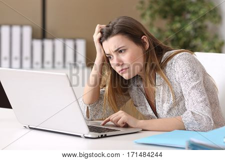 Confused trainee working on line with a laptop in a difficult assignment at office