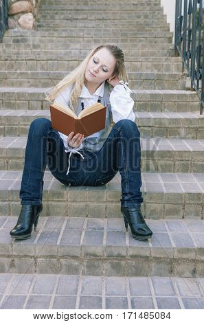 Portrait of Cute and Tranquil Caucasian Blond Woman Reading Book While Sitting Straight on Stairs Outdoors.Vertical Image Composition