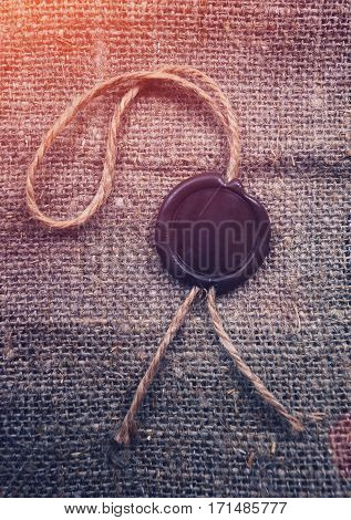 Sealing wax on sackcloth background. Free space for text on sealing wax stamp. Retro concept background.