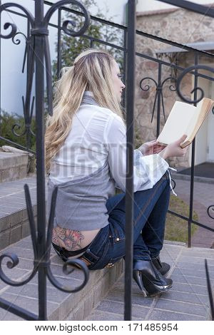 Reading Concepts and Ideas. Portrait of Tranquil Caucasian Blond Female With Book Sitting on Stairs Outdoors and Reading. Huge Flowery Tattoo on Back. Vertical Image Composition