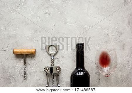 restaurant set with red wine bottle and corkscrew on white stone background top view mock-up
