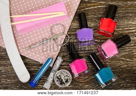 set for manicure and pedicure with various tool and nail Polish. On wooden background