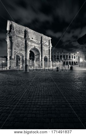 Arch of Constantine and Colosseum at night in Rome, Italy.