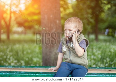 Little Boy Talking On The Phone While Sitting Outdoors