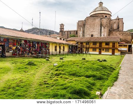 Rear view of Cusco cathedral where some shops offer colourful cloth bags, Peru