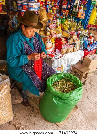 Cusco, Peru - December 13, 2011: Local woman offering Coca leaves while knitting, on a market in Cusco