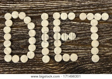 pills posted in word diet. On wood background