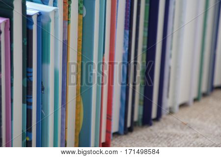 Pile of books standing in a row on the counter closeup