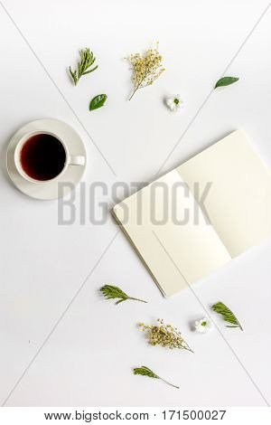 Blank copybook, cup of americano and fresh flowers on white table background top view mock-up