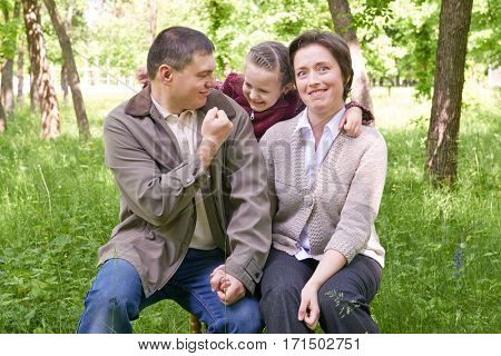 Strict man imitates violence and aggression. Family and child in summer park. Face expression.