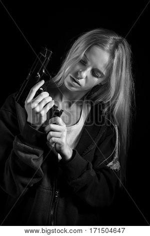 serious girl with gun on black background, monochrome