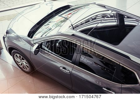 of the car in the spacious showroom with large windows.