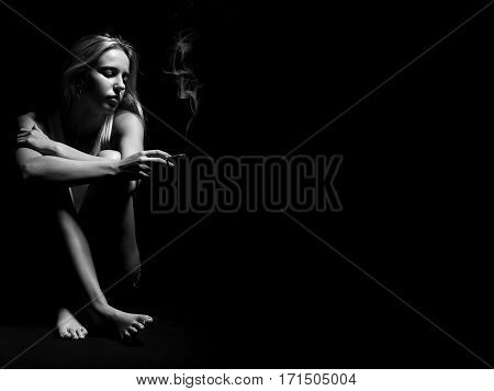 young woman sitting in dark smoking cigarette, monochrome image with copyspace