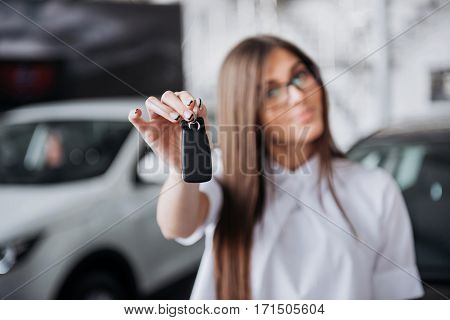 Portrait of a young beautiful woman looking at the camera at the car showing keys.