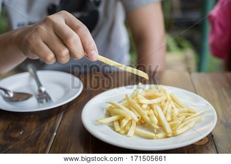 Asian Man Eating Potato Sticks Or French Fries At Restaurant On Sunday Weekend.