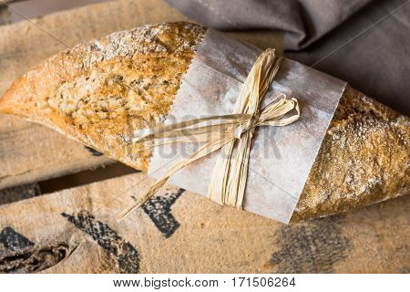 Rye whole wheat bread roll with golden crust wrapped in parchment paper on wood vintage box grey linen napkin top view close up