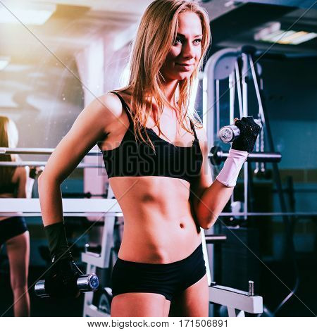 Fitness female woman with muscular body, doing her workout with dumbbells