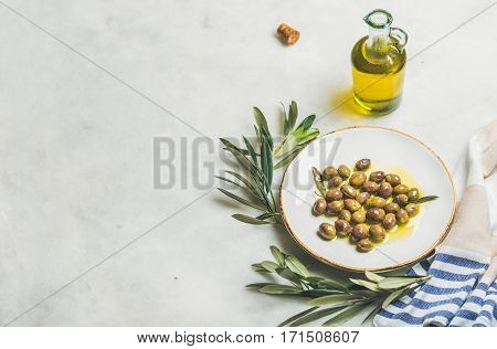 Pickled green Mediterranean olives in virgin olive oil on white ceramic plate, olive tree branch and olive oil in glass bottle over grey marble background, selective focus, copy space
