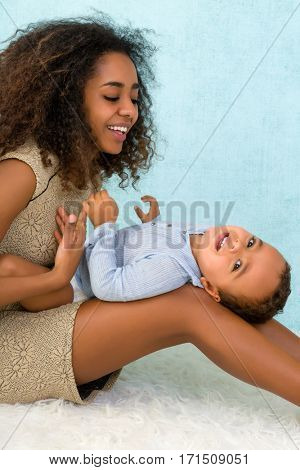 Happy African Ethiopian mother playing with her 18 month old little boy