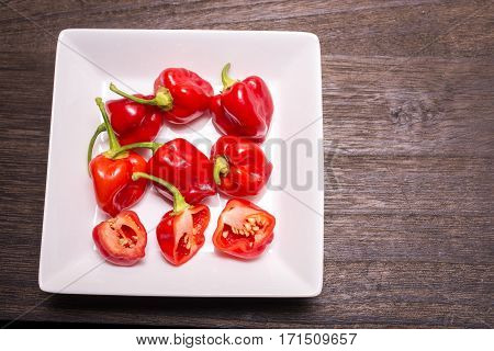 Several red habanero chilli fruit on white square plate