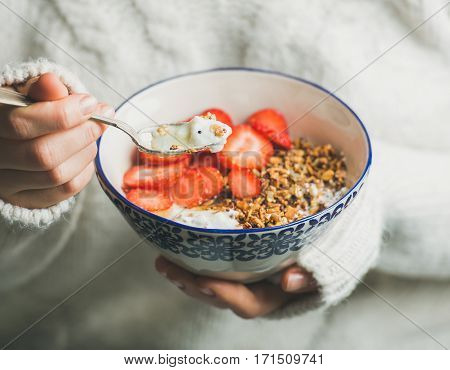 Healthy breakfast greek yogurt, granola and strawberry bowl in hands of woman wearing white loose knitted woolen sweater, selective focus. Clean eating, healthy, vegetarian, dieting food concept