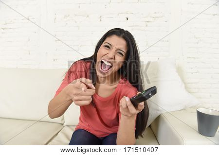 young beautiful and attractive latin woman at home sofa couch laughing and smiling happy watching television comedy movie or funny tv series alone pointing gesture