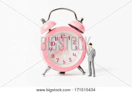 Vintage pink alarm clock and businessman miniature on white background. Working time concept.