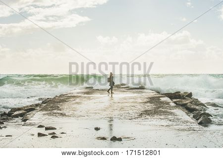 Silhouette of young woman walking on pier surrounded by stones and looking at waves of stormy Mediterranean sea in winter, Alanya, Turlkey