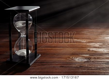 Time passing concept. Black hourglass with white sand on wooden background