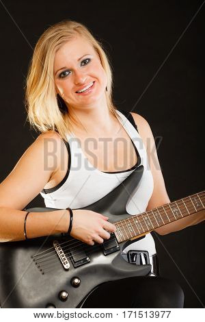 Music singing concept. Musically talented woman playing on electric guitar black background