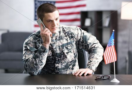 Soldier talking by mobile phone while sitting at table in headquarters building