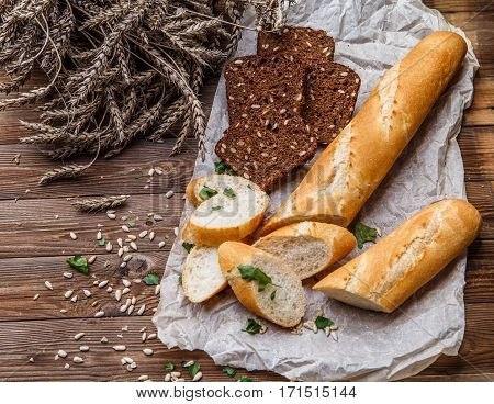 Wooden table with bread, sunflower seeds, wheat, parsley